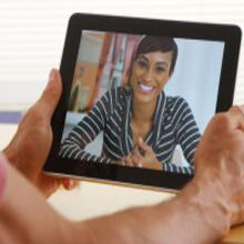Woman doing skype or facetime life coaching, counseling smiling and happy.
