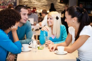 Photo of man socializing at ease with three women without blushing or anxiety.