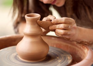 Woman scultping clay on a potters wheel, creating art and expressing herself and soul.