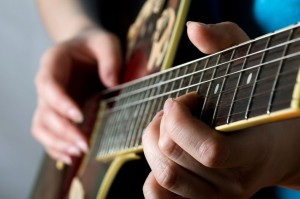 A person playing music on a quitar, you can see his or her hands creating and enjoying music.