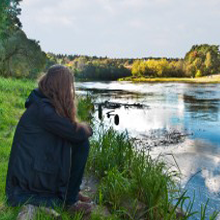 Woman sitting looking at lake feeling anxious, alone, depressed.