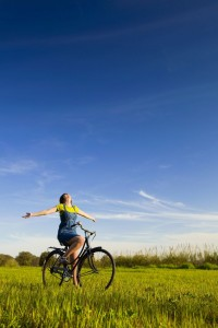 Women on bicycle with arms outstrethced riding through green grass, blue sky, feeling freedom and joy.