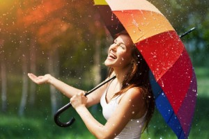 Very happy woman in summer rain with rainbow umbrella looking to sky laughing.