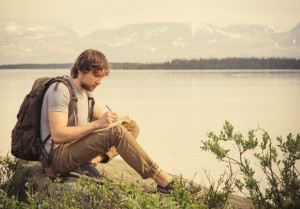 Man near lake, taking time out while hiking to write in his journal, express himself and reflect on his life.