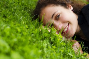 Happy woman lying in the grass free of concerns of self-image, eating disorders, and body-image issues.