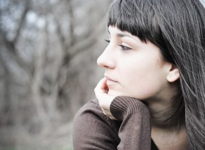 Woman looking away in deep thought about emotional issues she is having in her life, considering alternatives to psychotherapy or coaching..