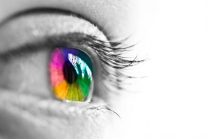 photo of a person's eye in black and white, with a pupil that has all the colors of the rainbow, a person that meditates and has a mindfulness practice