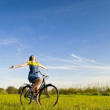 Woman riding on the bike, happy, who was helped with individual therapy.