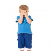 Boy in blue with hands over face to cover blushing and turning red