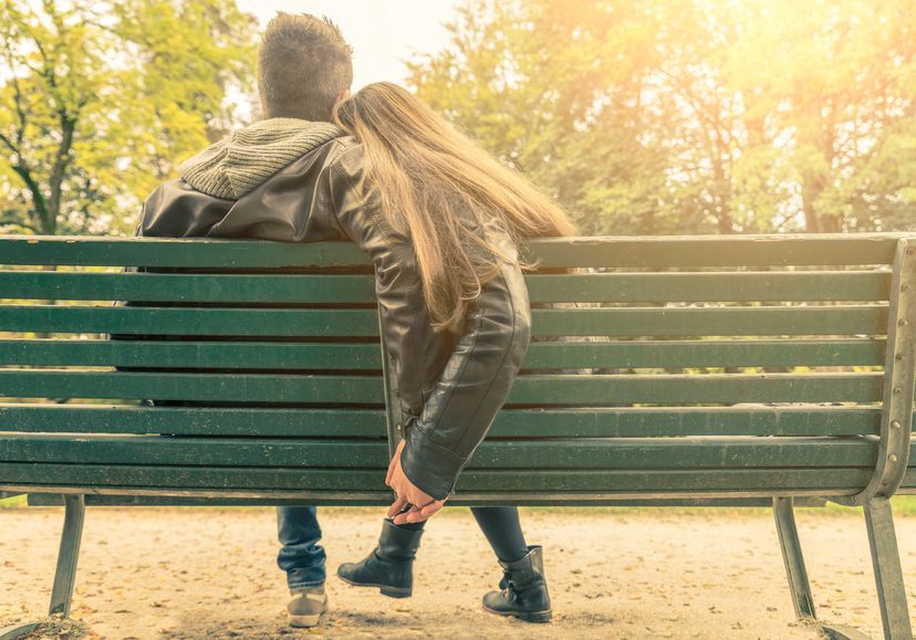 couple on a bench - two lovers sitting on a bench in a park and holding themselves by hands - concepts of autumn,love,togetherness, relationship
